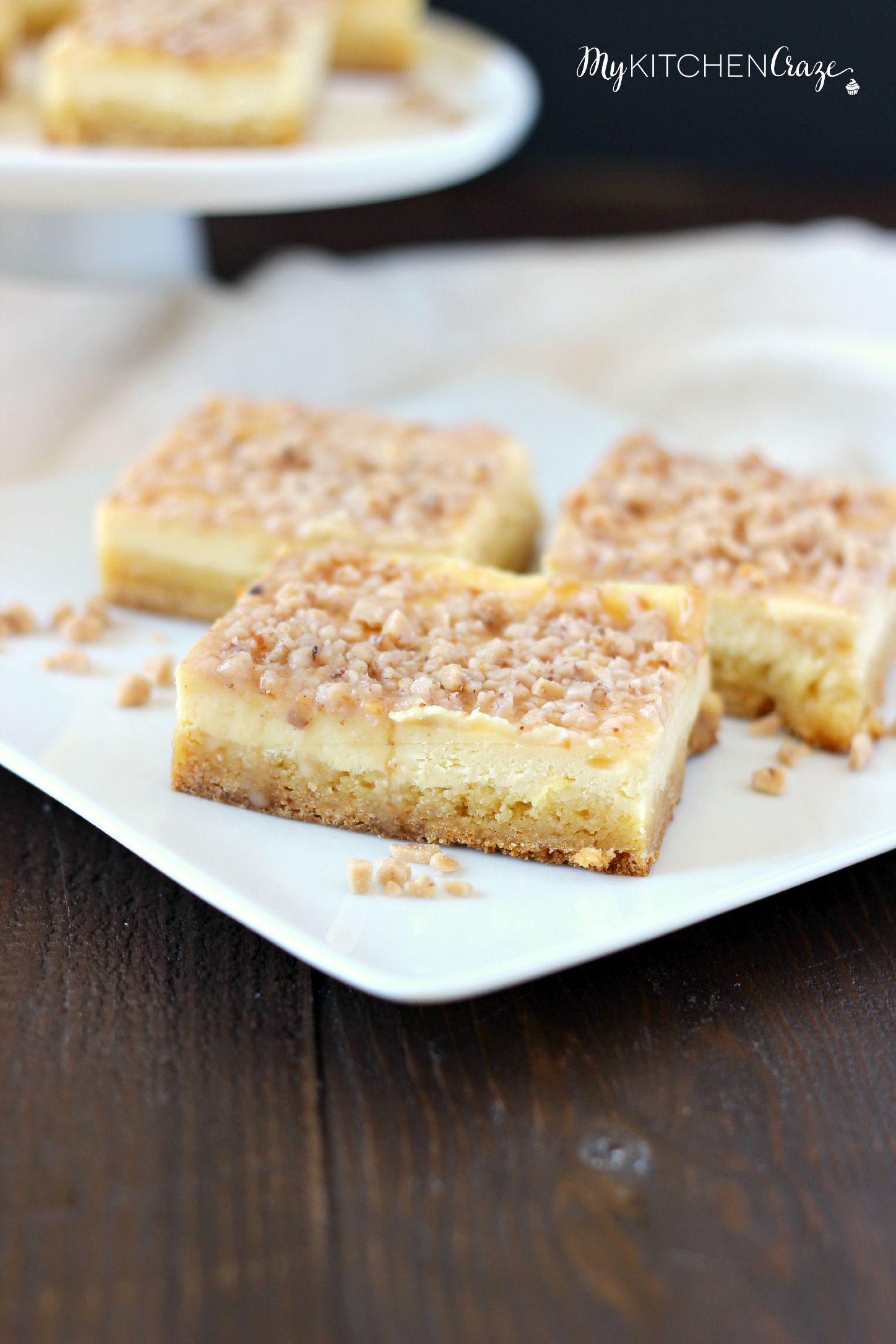 Toffee Cheesecake Bars ~ mykitchencraze ~ These bars are not only easy to throw together, but taste amazing! Sugar cookie bottom. Topped with a creamy cheesecake and sprinkled with toffee bits. What more could you ask for?