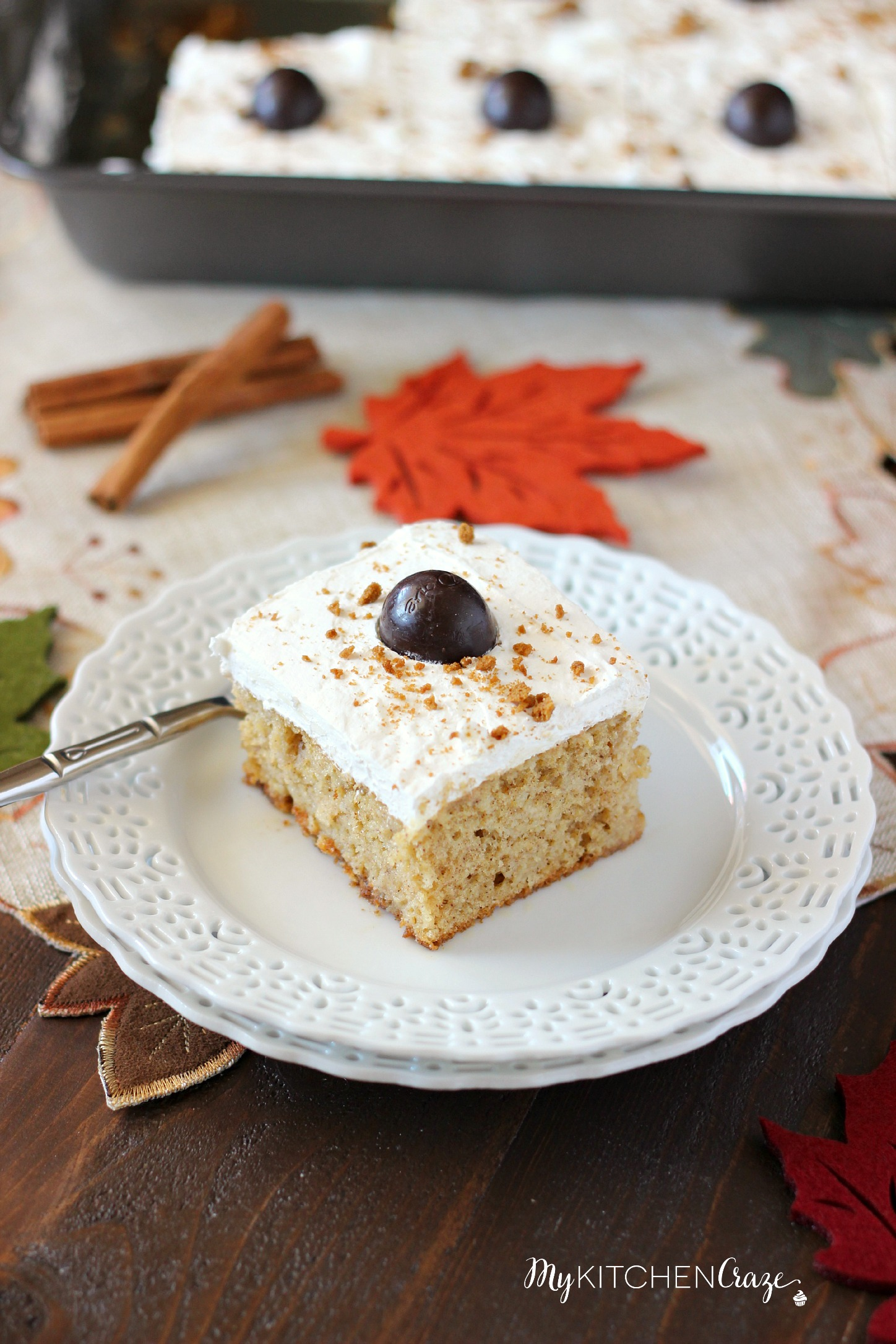 Spiced Pumpkin Poke Cake ~ mykitchencraze.com ~ Moist spiced pumpkin cake smothered with condensed milk, then topped with a cream cheese whipped frosting and a dark chocolate pumpkin. Delicious!